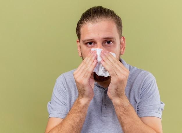 Nahaufnahme des schwachen jungen gutaussehenden kranken mannes, der seine nase mit serviette abwischt, die vorne auf olivgrüner wand lokalisiert betrachtet