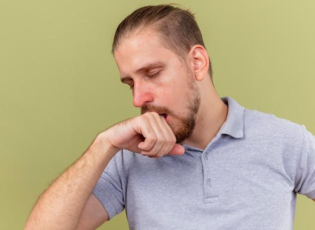 Nahaufnahme des schwachen jungen gutaussehenden slawischen kranken mannes, der mit geschlossenen augen hustet und hand nahe mund lokalisiert auf olivgrüner wand hält