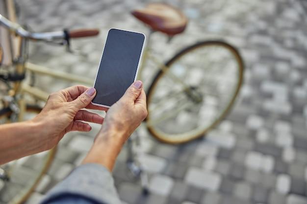 Nahaufnahme des schwarzen bildschirms eines modernen mobiltelefons in der hand einer frau, die auf der straße im park isoliert ist
