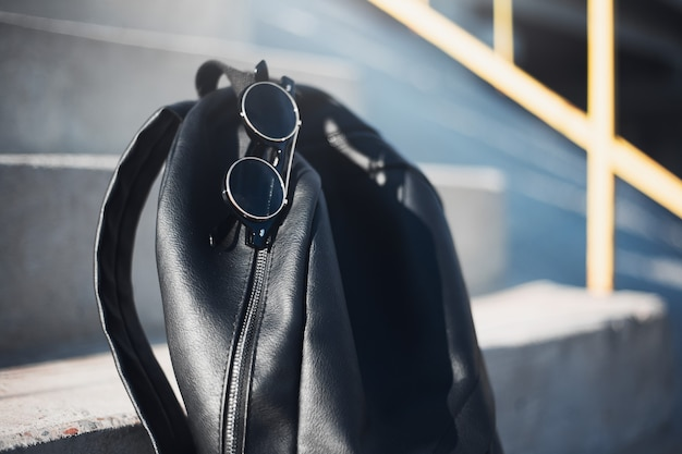 Nahaufnahme des schwarzen rucksacks und der runden sonnenbrille auf städtischen treppen.