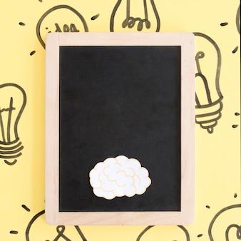Nahaufnahme des schwarzen schiefers mit gezeichnetem glühlampehintergrund des gehirns an hand