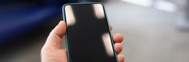 Nahaufnahme des schwarzen smartphonebildschirms in der personenhand. handy gesperrt. zeit am öffentlichen ort töten. modernes technologie- und kommunikationskonzept
