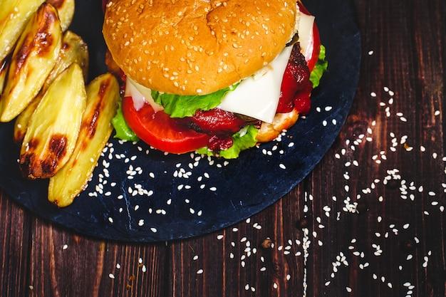 Nahaufnahme des selbst gemachten rindfleischburgers mit dem kopfsalat und kartoffel diente