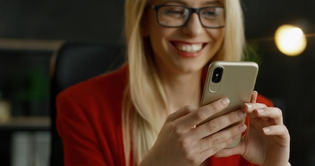Nahaufnahme des smartphones in den händen der blonden geschäftsfrau. glückliche weibliche sms-nachricht und tippen auf handy im schrank.