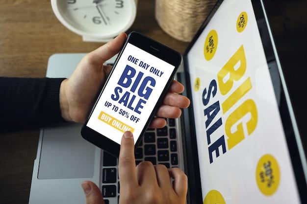 Nahaufnahme des smartphones mit weißem bildschirm und zeichen - big sale in weiblicher hand. im hintergrund unscharfes notizbuch. frau mit dem gadget zum surfen im internet, online-shopping, store-app.