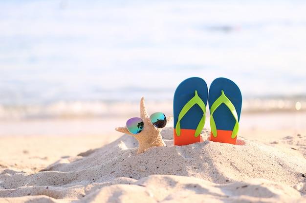 Nahaufnahme des sommerstrandes mit blauen flipflops und sonnenbrille auf starfish im tropischen strand