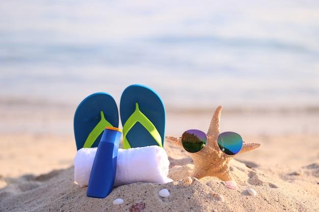 Nahaufnahme des sommerstrandes mit zubehör von blauen flipflops, von sonnenschutzcreme, von tuch und von sonnenbrille auf starfish im tropischen strand