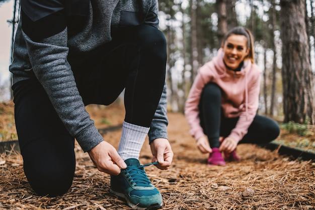 Nahaufnahme des sportlers, der seinen schnürsenkel bindet, während er im herbst im wald kniet. im hintergrund bindet auch seine freundin schnürsenkel.