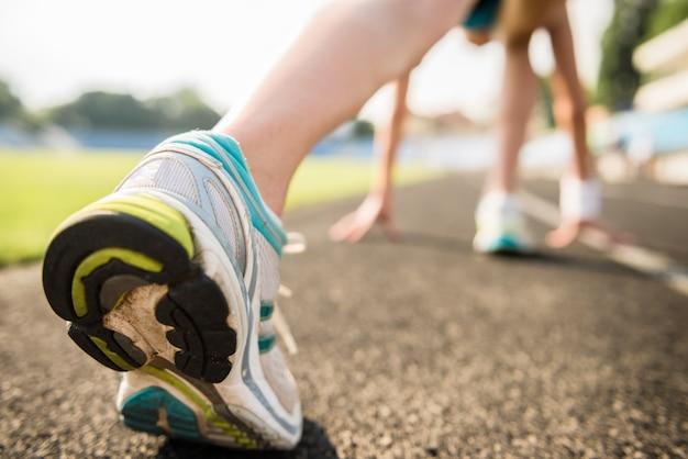 Nahaufnahme des sportlichen mädchens bereit, sprint laufen zu lassen.