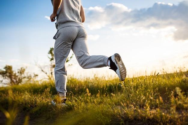 Nahaufnahme des sportlichen mannes, der im feld bei sonnenaufgang joggt.