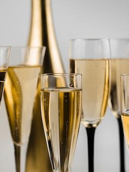 Nahaufnahme des sprudelnden champagners mit goldener flasche