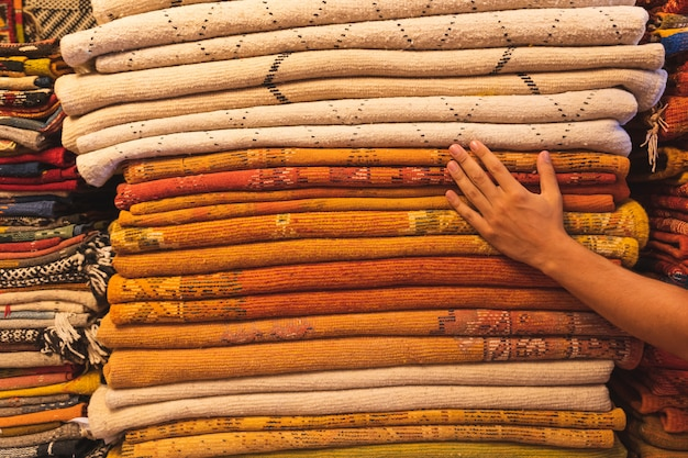 Nahaufnahme des stapels der bunten teppiche in einem markt in marokko