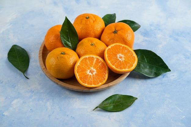 Nahaufnahme des stapels der clementinenmandarine auf hölzernem teller