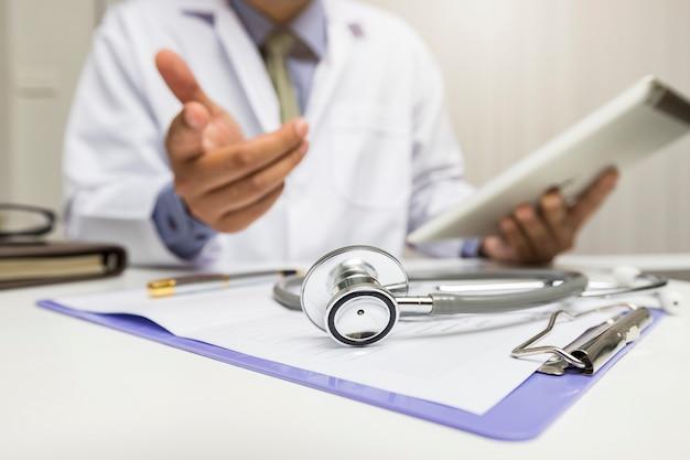 Nahaufnahme des stethoskops liegt auf dem klemmbrett nahe einem doktor.