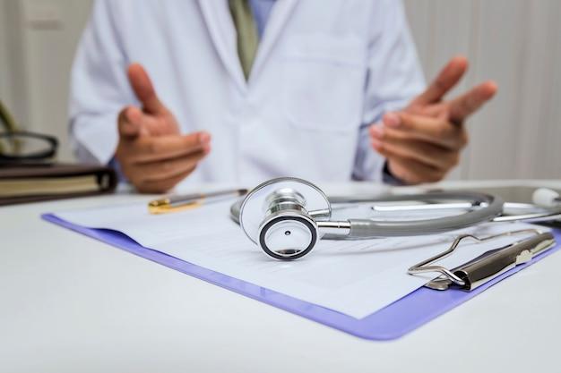 Nahaufnahme des stethoskops liegt auf dem klemmbrett vor einem doktor.