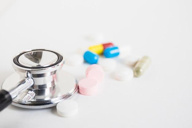 Nahaufnahme des stethoskops mit bunten pillen auf weißem hintergrund