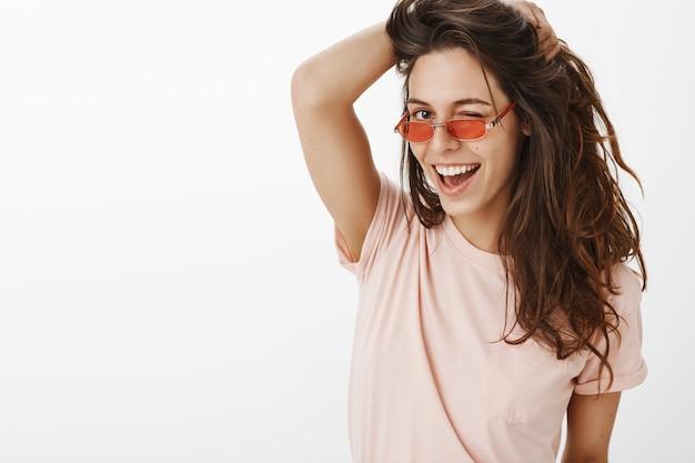 Nahaufnahme des stilvollen mädchens mit der sonnenbrille, die gegen die weiße wand aufwirft