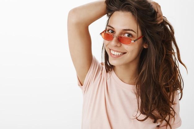 Nahaufnahme des stilvollen schönen mädchens mit der sonnenbrille, die gegen die weiße wand aufwirft