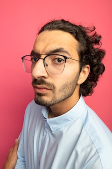 Nahaufnahme des strengen jungen gutaussehenden kaukasischen mannes, der brillen trägt, die in der profilansicht lokalisiert auf purpurroter wand stehen