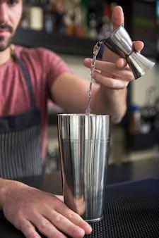Nahaufnahme des strömenden cocktails des barmixers im schüttel-apparat am barzähler
