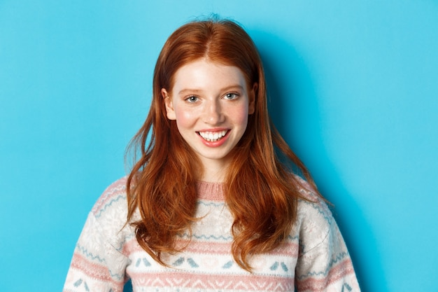 Nahaufnahme des süßen rothaarigen mädchens im pullover, das glücklich in die kamera lächelt und vor blauem hintergrund steht.