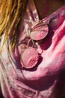 Nahaufnahme des t-shirts und der sonnenbrille der frau verwirren mit holi farbe