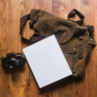 Nahaufnahme des tagebuchs und der tasche mit kamera auf hölzernem schreibtisch