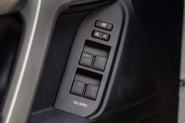 Nahaufnahme des tastensteuerungsfensters im modernen autoinnenraum. details des fahrzeuginnenraums. türgriff mit fenstersteuerung