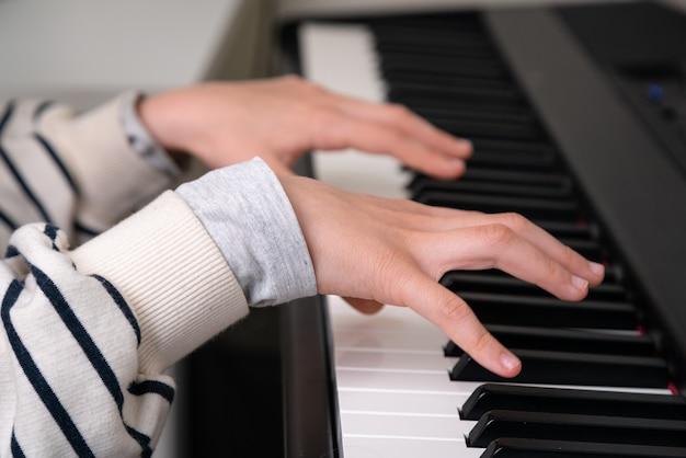 Nahaufnahme des teenagers, der klavier im heimmusikstudio spielt.