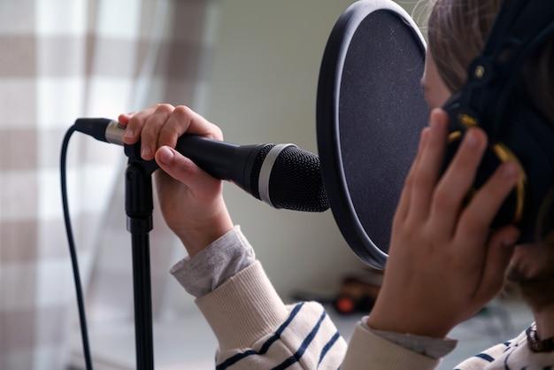 Nahaufnahme des teenagers, der musik im heimstudio aufnimmt. mädchen mit kopfhörern und mikrofonaufnahmelied