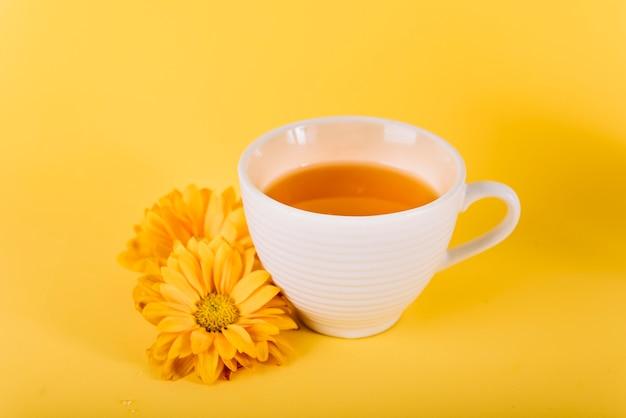 Nahaufnahme des tees und der blumen auf gelbem hintergrund