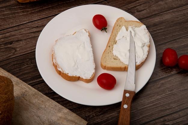 Nahaufnahme des tellers der weißbrotscheiben verschmiert mit hüttenkäse und tomaten und messer auf hölzernem hintergrund