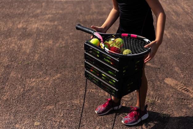 Nahaufnahme des tennisjugendmädchens nahe der schachtel der bälle auf dem platz