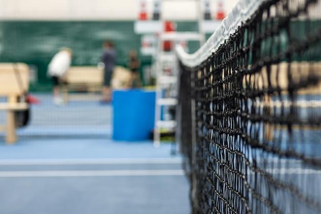 Nahaufnahme des tennisplatzes durch das netz