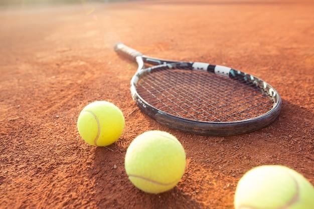 Nahaufnahme des tennisschlägers und der bälle auf dem sandtennisplatz