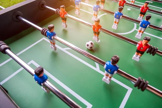 Nahaufnahme des tischfußballfußballspiels auf grünem feld