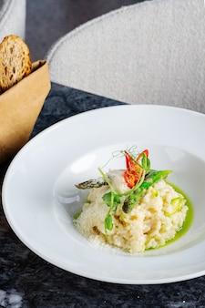 Nahaufnahme des traditionellen und leckeren risottos mit parmesan, spargel und chili. mediterrane und italienische küche. weicher, selektiver fokus. mit spargel aufgehen lassen.