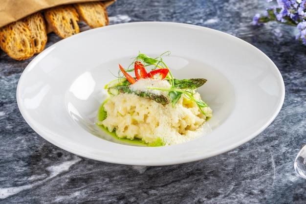 Nahaufnahme des traditionellen und leckeren risottos mit parmesan, spargel und chili