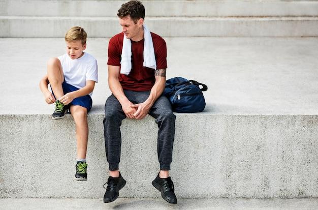 Nahaufnahme des trainers sitzend auf schritt mit dem jungen, der trainerrobe bindet