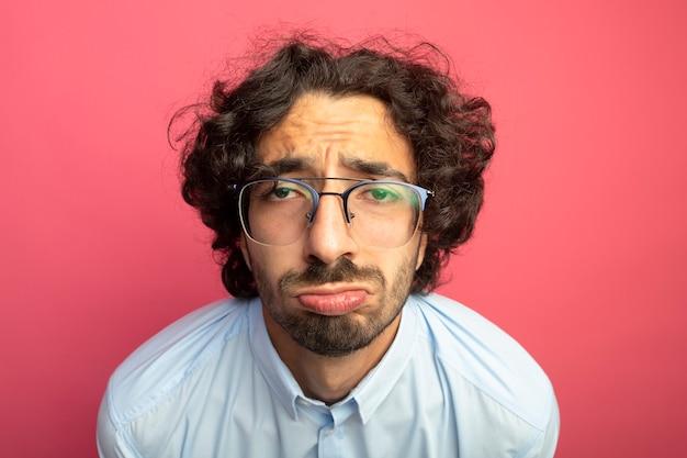 Nahaufnahme des traurigen jungen gutaussehenden mannes, der brillen trägt, die front lokalisiert auf rosa wand betrachten