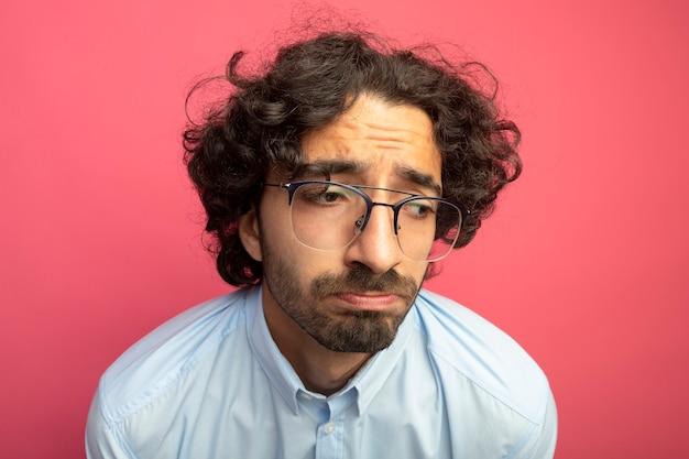 Nahaufnahme des traurigen jungen gutaussehenden mannes, der gläser trägt, die seite lokalisiert auf rosa wand betrachten