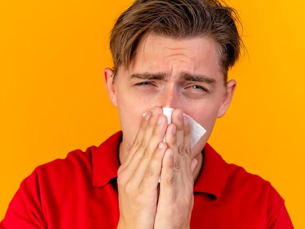 Nahaufnahme des traurigen jungen hübschen blonden kranken mannes, der die vordere wischnase mit der serviette lokalisiert auf orange wand betrachtet