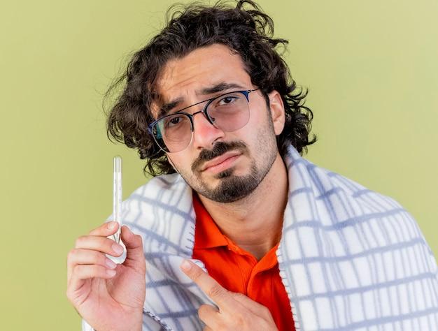 Nahaufnahme des traurigen jungen kranken mannes, der die brille trägt, die im karierten haltethermometer eingewickelt wird, das front lokalisiert auf olivgrüner wand betrachtet