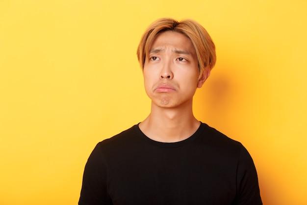 Nahaufnahme des traurigen und enttäuschten gutaussehenden asiatischen kerls, der verärgert schmollt und mit bedauern oder eifersucht in die obere linke ecke schaut und gelbe wand steht