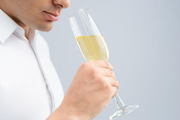 Nahaufnahme des trinkenden champagners des mannes vom becher