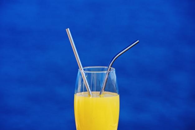 Nahaufnahme des trinkglases mit orangensaft und metallischen strohen gegen blau