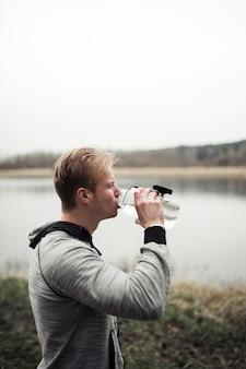 Nahaufnahme des trinkwassers des jungen mannes von der flasche