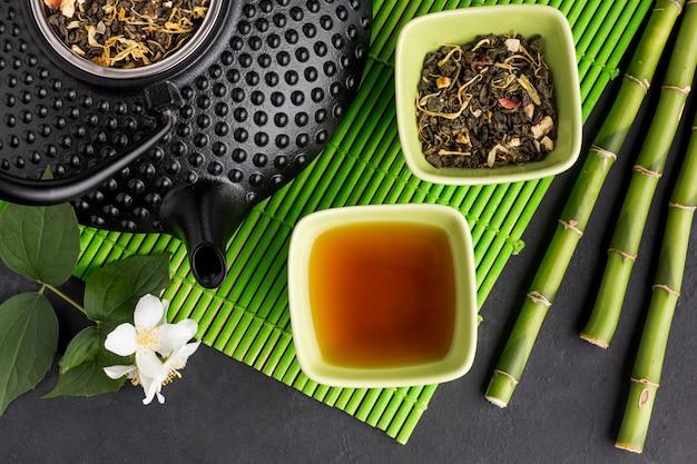 Nahaufnahme des trockenen tee- und bambusstocks mit dem weißen jasminblumenzweig