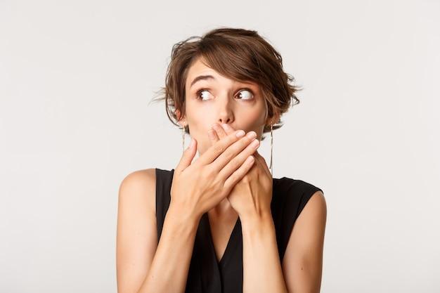 Nahaufnahme des überraschten mädchens, das nach luft schnappt, den mund mit den händen bedeckt und nach links schaut und über weiß steht.