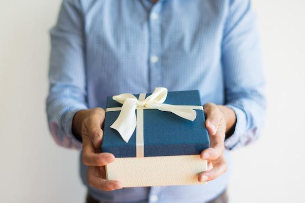 Nahaufnahme des unerkennbaren mannes, der kamera geschenkbox gibt